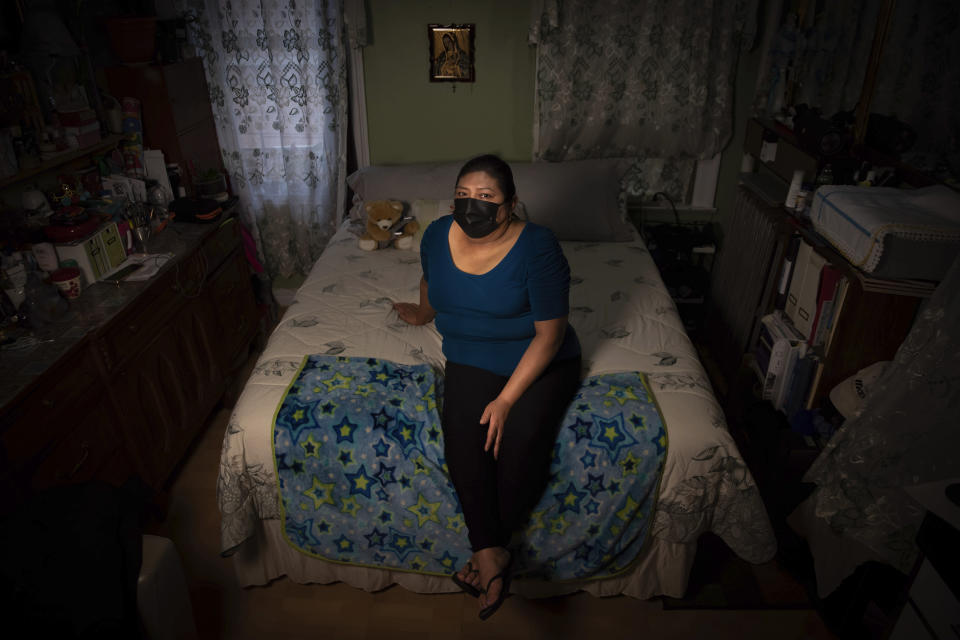 Candida Uraga poses for a photo in the bedroom she rents in New York on Friday, March 19, 2021. She has struggled to pay rent after being laid off from her job as a teaching assistant during the pandemic and was denied help under a federally-funded rental assistance program. (AP Photo/Robert Bumsted)
