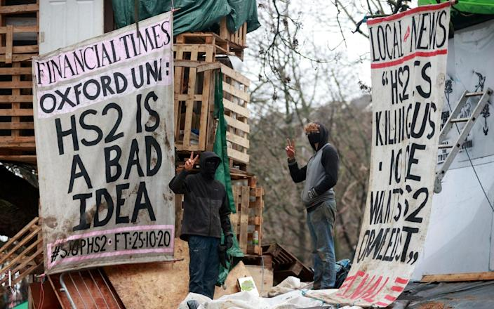 Extinction Rebellion activists gesture next to signs at a makeshift camp as part of an HS2 protest - Reuters