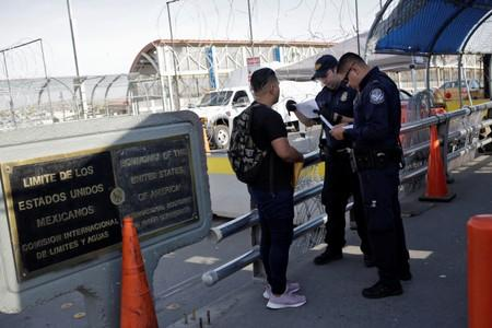 U.S. Customs and Border Protection officers inspect documents from a Central American migrant seeking asylum at Paso del Norte International border bridge, in this picture taken from Ciudad Juarez