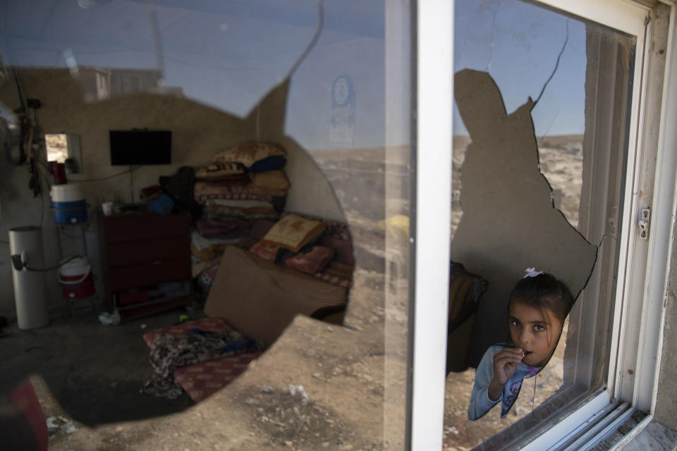 A Palestinian girl is seen through her family house's shattered window following a settlers' attack from nearby settlement outposts on the Bedouin community, in the West Bank village of al-Mufagara, near Hebron, Thursday, Sept. 30, 2021. Israeli settler attack last week damaged much of the village's fragile infrastructure. (AP Photo/Nasser Nasser)
