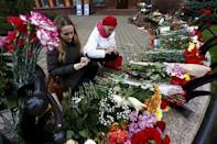 Women light candles to commemorate victims of the Paris attacks, in front of the French embassy in Minsk, Belarus November 16, 2015. REUTERS/Vasily Fedosenko