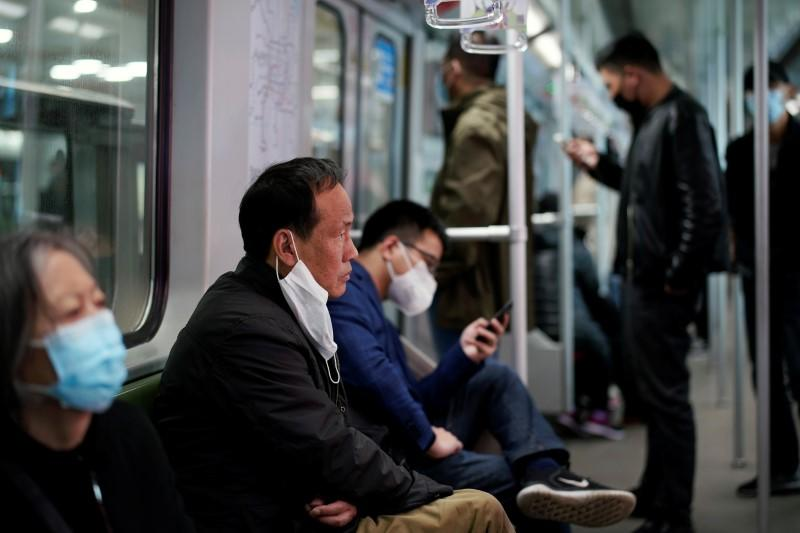 Passengers with face masks ride a subway after the city's emergency alert level for coronavirus disease (COVID-19) was downgraded, in Shanghai,