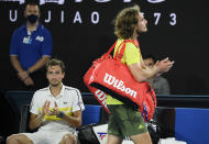 Greece's Stefanos Tsitsipas, right, walks past Russia's Daniil Medvedev as he leaves Rod Laver Arena after losing his semifinal at the Australian Open tennis championship in Melbourne, Australia, Friday, Feb. 19, 2021.(AP Photo/Andy Brownbill)