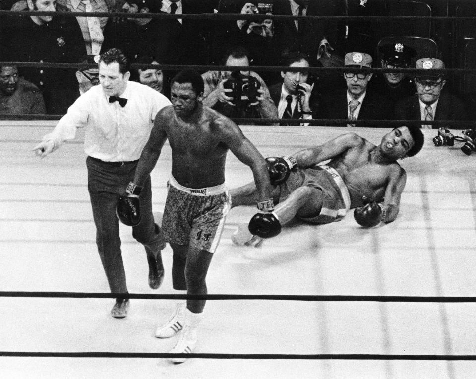 <p>Boxer Joe Frazier being directed to the ropes by referee Arthur Marcante after knocking down Muhammad Ali during the 15th round of the title bout at Madison Square Garden in New York on March 8, 1971. (AP Photo)</p>