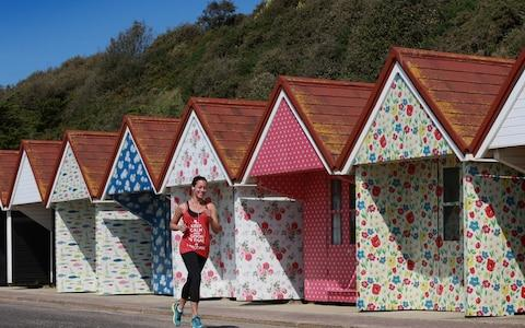 A jogger passes by the beach huts at Bournemouth Beach in Dorset, which have been decorated in Cath Kidston prints - Credit:  Matt Alexander