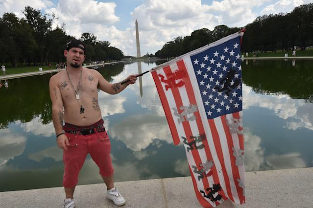 <p>A fan of the US rap group Insane Clown Posse, known as Juggalos, poses with a national flag as several thousand fans prepare on Sept. 16, 2017 to assemble near the Lincoln Memorial in Washingtonto protest at a 2011 FBI decision to classify their movement as a gang. (Photo: Paul J. Richards/AFP/Getty Images) </p>