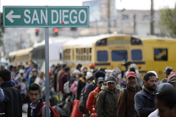 <p>Central American migrants line up for a meal at a shelter in Tijuana, Mexico, Wednesday, Nov. 14, 2018. Migrants in a caravan of Central Americans scrambled to reach the U.S. border, catching rides on buses and trucks for hundreds of miles in the last leg of their journey Wednesday as the first sizable groups began arriving in the border city of Tijuana. (Photo: Gregory Bull/AP) </p>
