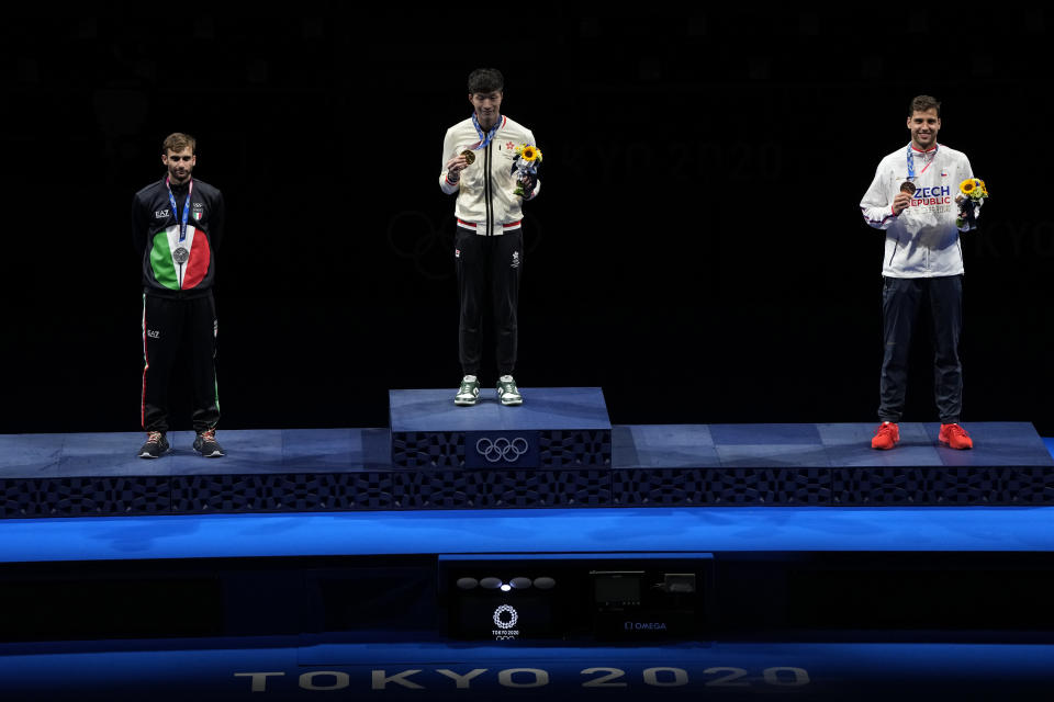 From left, silver medal Daniele Garozzo of Italy, gold medal Ka Long Cheung of Hong Kong and bronze medal Alexander Choupenitch of the Czech Republic celebrate on the podium of the men's individual Foil final competition at the 2020 Summer Olympics, Monday, July 26, 2021, in Chiba, Japan. (AP Photo/Hassan Ammar)