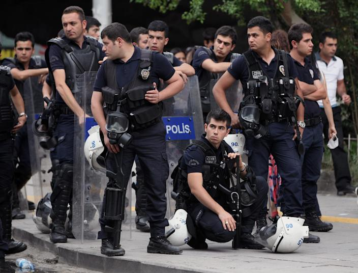 Riot police stand by near a rally by the labor unions in Ankara, Turkey, Monday, June 17, 2013. A day earlier, riot police cordoned off streets, set up roadblocks and fired tear gas and water cannons to prevent anti-government protesters from an effort to return to Taksim Square in Istanbul. Labor unions and political foes of Prime Minister Recep Erdogan rallied Monday by the thousands across Turkey, hoping to capitalize on weeks of protest that began as small-scale activism and parlay it into a chance to register broader discontent.(AP Photo/Burhan Ozbilici)
