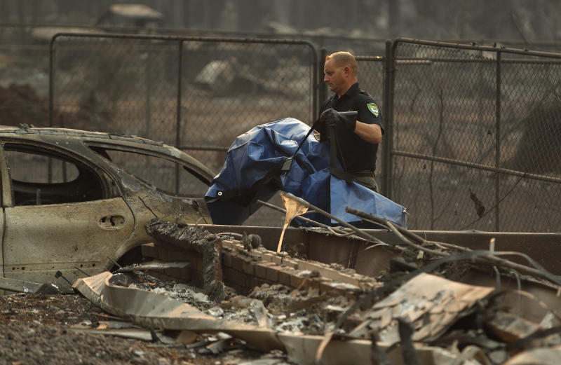 Sgt. Nathan Lyberger, of the Yuba County Sheriff's Department, carries a bag with human remains found at a burned out home at the Camp Fire, Sunday, Nov. 11, 2018, in Paradise, Calif. (AP Photo/John Locher)