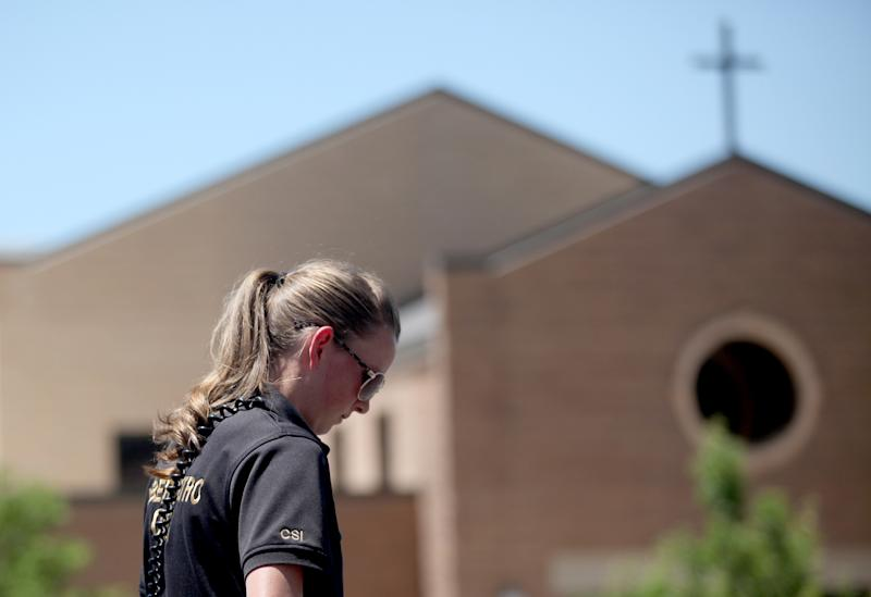 Crime scene investigators examiner the parking lot outside of St. James Catholic Church in Ogden, Utah, where a man was shot in the back of the head during Sunday Mass on June 16, 2013. Charles Richard Jennings Jr., 35, was arrested Sunday afternoon in nearby Box Elder County after fleeing in a stolen pickup truck, investigators said. (AP Photo/Standard-Examiner, Benjamin Zack) TV OUT; MANDATORY CREDIT