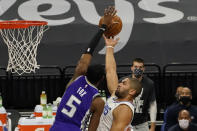 Sacramento Kings guard De'Aaron Fox, left, contests the shot of Los Angeles Clippers forward Nicolas Batum during the first quarter of an NBA basketball game in Sacramento, Calif., Friday, Jan. 15, 2021. (AP Photo/Rich Pedroncelli)