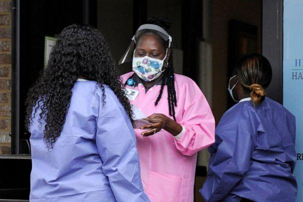 PHOTO: Health care workers talk outside a Lowndes County coronavirus testing site in Hayneville, Ala., May 27, 2020. (Jay Reeves/AP, FILE)