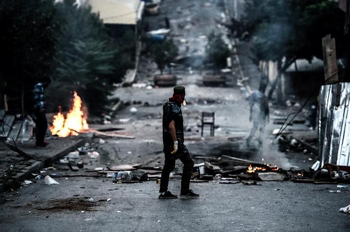 A left-wing protester walks in front of a barricade during clashes with Turkish riot police in the district of Gazi, Istanbul on July 26, 2015 (AFP Photo/Ozan Kose)