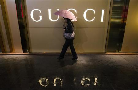 A woman holding an umbrella walks past a company logo of a Gucci boutigue outside a shopping mall amid rainfalls in central Guangzhou