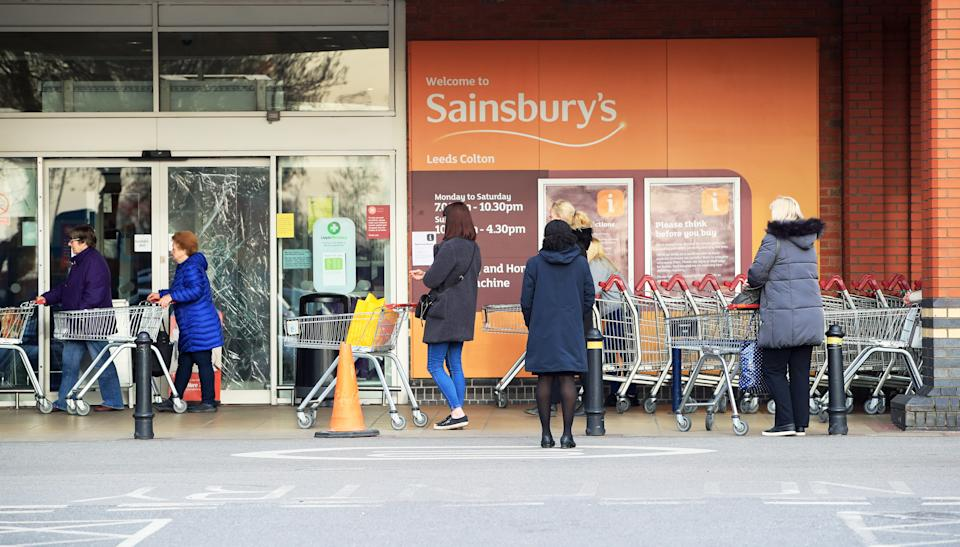 People observe social distancing while queuing at a Sainsbury's supermarket at Colton, on the outskirts of Leeds, the day after Prime Minister Boris Johnson put the UK in lockdown to help curb the spread of the coronavirus.