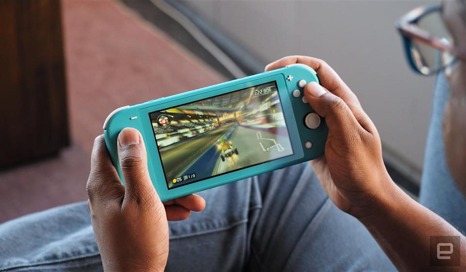 An over-the-shoulder view of someone playing a Nintendo Switch Lite portable gaming device.