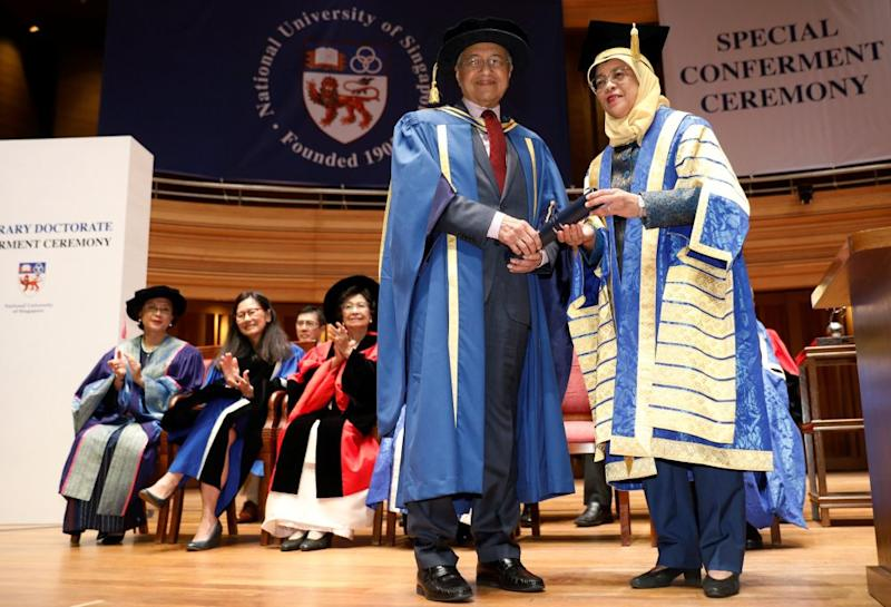 Malaysia's Prime Minister Tun Dr Mahathir Mohamad is conferred an honorary Doctor of Laws degree by Singapore's President Halimah Yacob at the National University of Singapore November 13, 2018. — Reuters pic