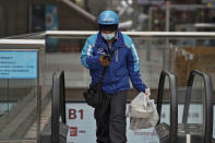 A food delivery worker wearing a face mask to help curb the spread of the coronavirus prepares to deliver foods for his customers at a shopping mall in Beijing on Thursday, Jan. 14, 2021. The e-commerce workers and delivery people who kept China fed during the pandemic, making their billionaire bosses even richer, are so unhappy with their pay and treatment that one just set himself on fire in protest. (AP Photo/Andy Wong)
