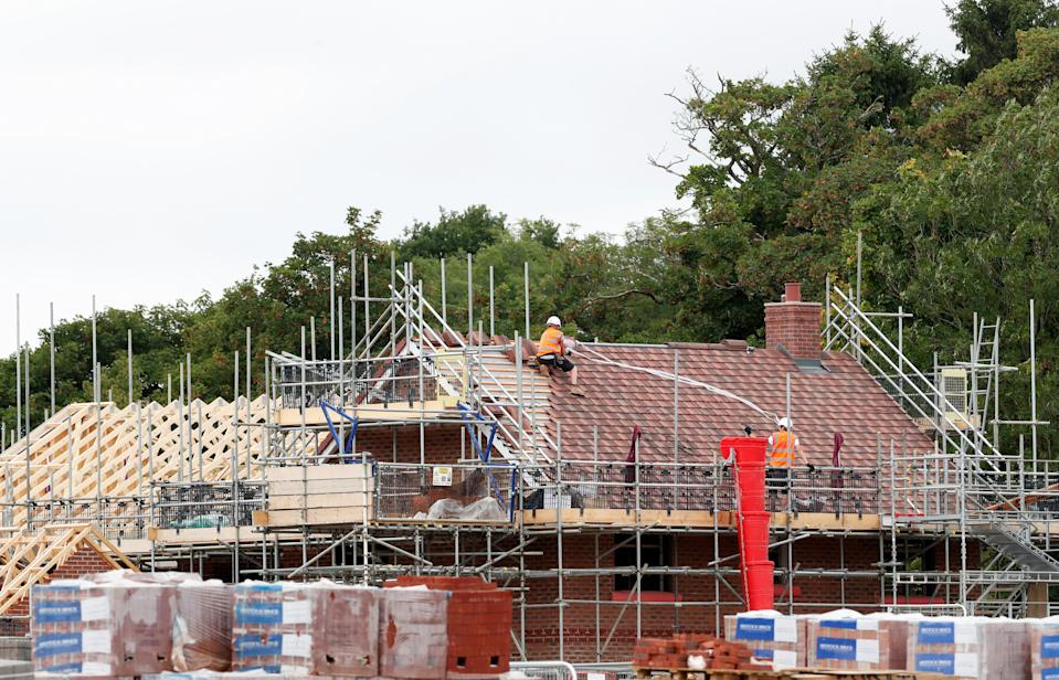Construction workers build a new house in Berkhamsted, Britain August 6, 2020. REUTERS/Matthew Childs