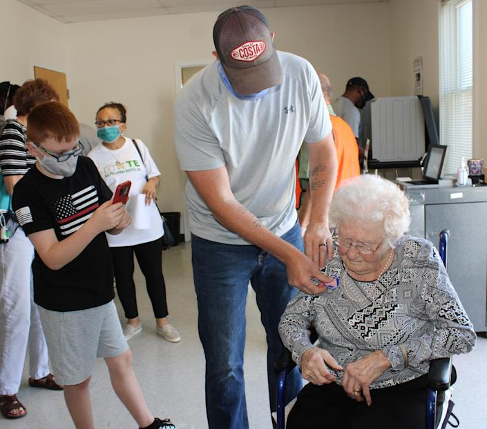 """Curtis Litton places an """"I voted"""" sticker on his grandmother Centenarian Mabel Dorothy Duty Cook after she cast her ballot at the Registrar's Office in Chesterfield on Oct. 15, 2020 while Cook's great-grandson Jack Litton records the monumental event."""
