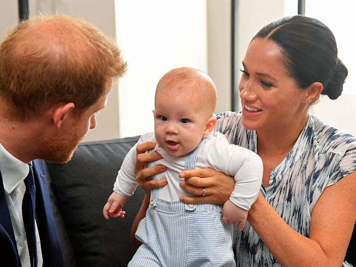 Meghan Markle holds Archie as Prince Harry looks at him.