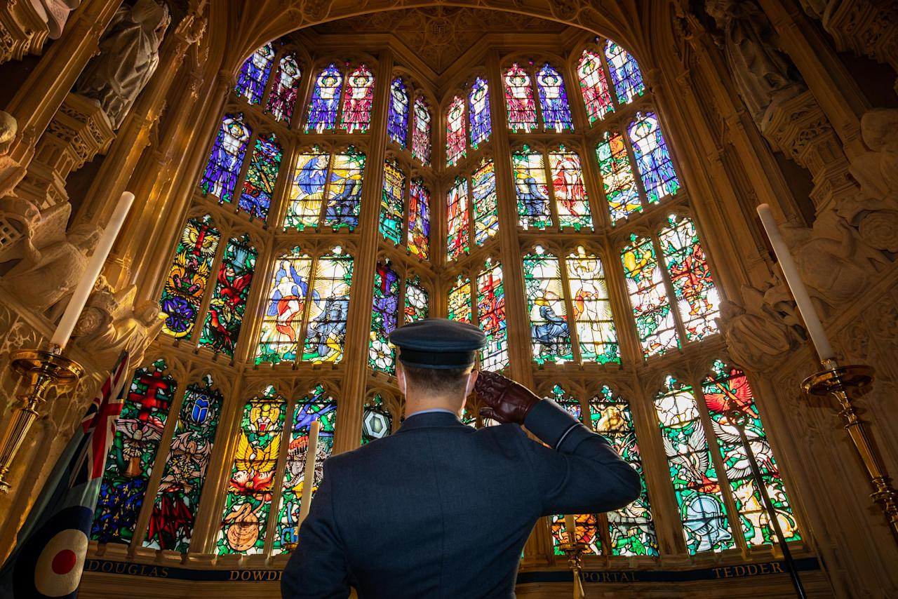Flying Officer James Buckingham salutes The Battle of Britain memorial window inside Westminster Abbey, the stained glass window by Hugh Easton that contains the badges of the fighter squadrons that took part in the Battle.