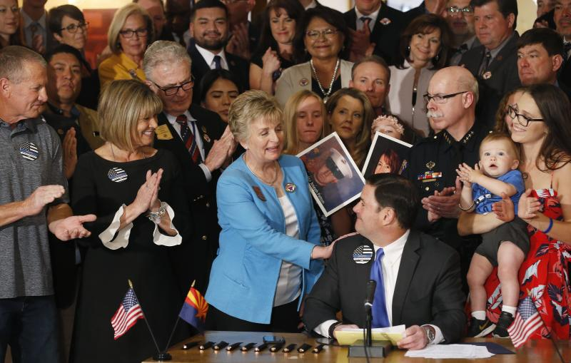 Arizona Republican Gov. Doug Ducey, seated, smiles as he gets a pat on the shoulder from bill sponsor Sen. Kate Brophy McGee, third from left, R-Phoenix, as the governor signs into law a distracted driving bill during a ceremony at the Arizona Capitol Monday, April 22, 2019, in Phoenix. Arizona becomes the 48th state to ban texting and the 18th to ban any hand-held phone use while driving. Officers can begin issuing warnings immediately and can write tickets in 2021. (AP Photo/Ross D. Franklin)