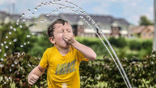PHOTO: Owen Boarman, 3, holds his nose as he runs through water spray on a hot day, July 17, 2019, in Owensboro, Ky. (Greg Eans/The Messenger-Inquirer via AP)