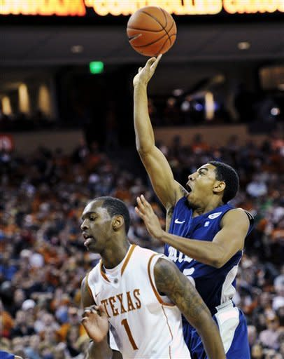 Rice guard Julian DeBose, right, puts up a shot against Texas guard Sheldon McClellan during the first half of an NCAA college basketball game, Saturday, Dec. 31, 2011, in Austin, Texas. (AP Photo/Michael Thomas)