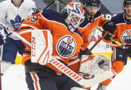 Edmonton Oilers goalie Mikko Koskinen (19) makes a save against the Toronto Maple Leafs during first-period NHL hockey game action in Edmonton, Alberta, Monday, March 1, 2021. (Jason Franson/The Canadian Press via AP)