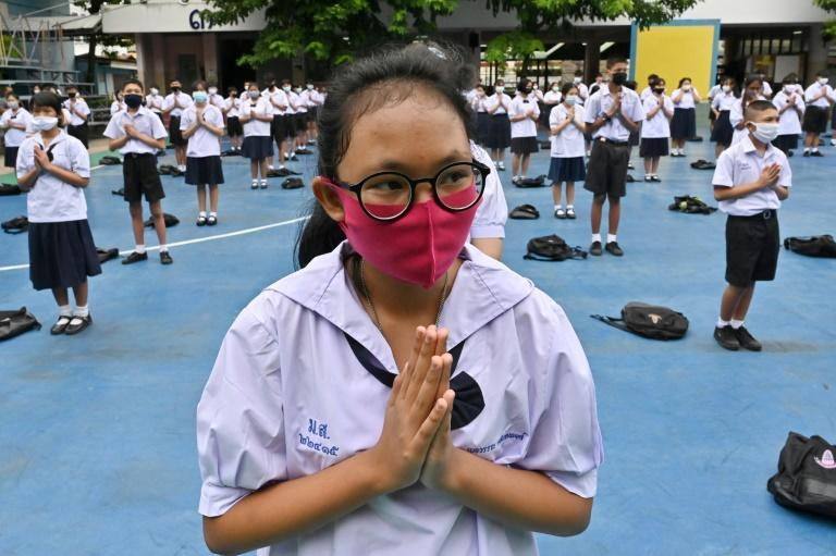 Students, socially distanced, attend a flag-raising ceremony at a secondary school in Bangkok