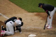 New York Yankees manager Aaron Boone, right, looks on as staff attend to Aaron Hicks, left, after he slipped during the eighth inning of a baseball game against the Washington Nationals at Yankee Stadium, Sunday, May 9, 2021, in New York. Hicks recovered and was able to complete his at-bat. (AP Photo/Seth Wenig)