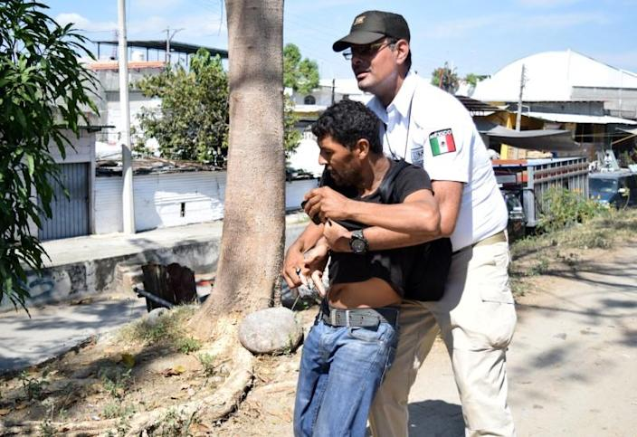 An agent of the National Migration Institute (INM) detains a migrant, part of a caravan travelling to the U.S., near the border between Guatemala and Mexico, in Ciudad Hidalgo