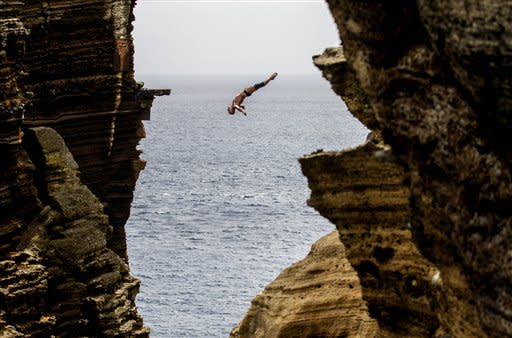 This photo made available by Red Bull shows Artem Silchenko of Russia diving 29 metres from the rock monolith during the first round of the third stop of the Red Bull Cliff Diving World Series in Islet Vila Franca do Campo, Azores, Portugal, Friday July 20, 2012. Kent De Mond of the USA leads after the first round with the remaining three rounds taking place Saturday. (AP Photo/Red Bull, Dean Treml)