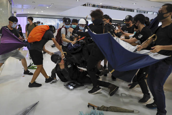 A policeman is attacked by protesters inside a mall in Sha Tin District in Hong Kong, Sunday, July 14, 2019. Police in Hong Kong have fought with protesters as they broke up a demonstration by thousands of people demanding the resignation of the Chinese territory's chief executive and an investigation into complains of police violence. (AP Photo/Kin Cheung)