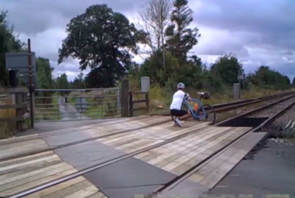 A cyclist is seen wedging his bike in the tracks to help a rider through the gate on to the crossing. (SWNS)