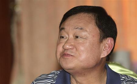 Former Thai prime minister, Thaksin Shinawatra smiles to his supporters at a hotel in Siem Reap province