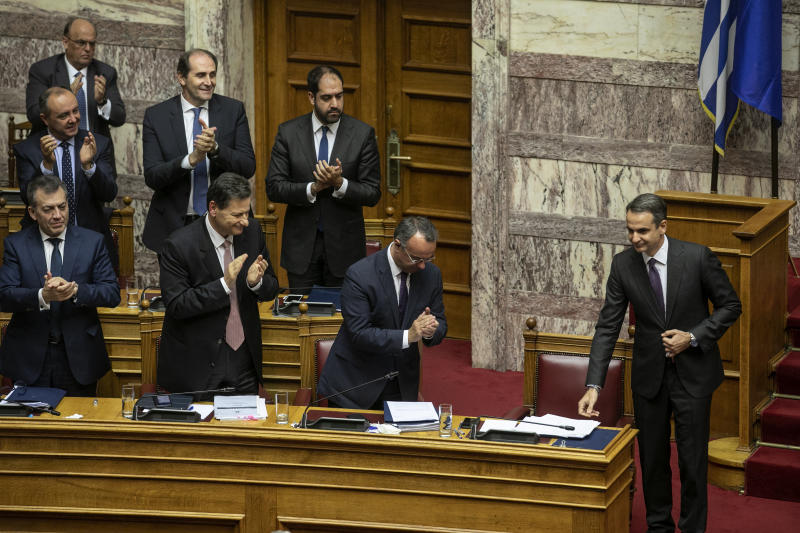 Greece's Prime Minister Kyriakos Mitsotakis, right, is applauded by lawmakers of his party following his speech during a parliament session in Athens, on Wednesday, Dec. 18, 2019. Greek lawmakers debate on the state budget for 2020. (AP Photo/Yorgos Karahalis)
