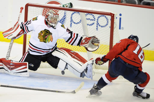 Washington Capitals right wing Eric Fehr, right, scores a goal against Chicago Blackhawks goalie Antii Raanta, left, of Finland, during the second period an NHL preseason hockey game on Friday, Sept. 20, 2013, in Washington. (AP Photo/Nick Wass)
