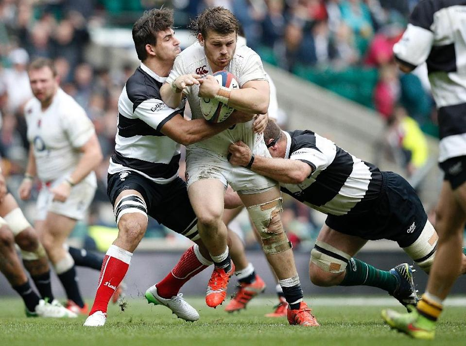 England's hooker Luke Cowan-Dickie (C) is tackled during their rugby union match against Barbarians, at Twickenham Stadium in south-west London, on May 31, 2015 (AFP Photo/Adrian Dennis)