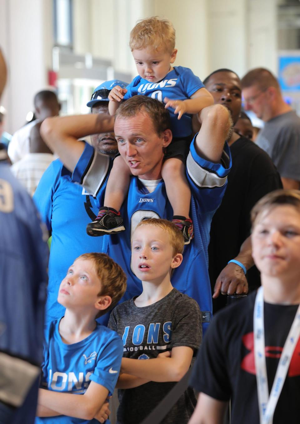 Mike Roberston and his sons, Levi 1, Aiden, 8, and Daniel, 7, wait in line during Detroit Lions practice at Family Fest, Friday, August 2, 2019 at Ford Field.