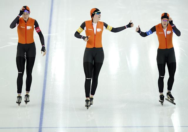 Jorien ter Mors, Lotte van Beek and Ireen Wust of the Netherlands congratulate each other after competing in the women's speedskating team pursuit quarterfinals at the Adler Arena Skating Center during the 2014 Winter Olympics in Sochi, Russia, Friday, Feb. 21, 2014. (AP Photo/Pavel Golovkin)