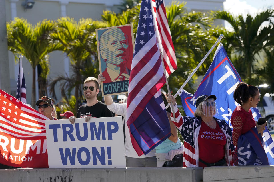 Supporters of President Donald Trump wait for the motorcade on the road to Mar-a-Lago, Trump's Palm Beach estate, on Wednesday, Jan. 20, 2021, in West Palm Beach, Fla. (AP Photo/Lynne Sladky)