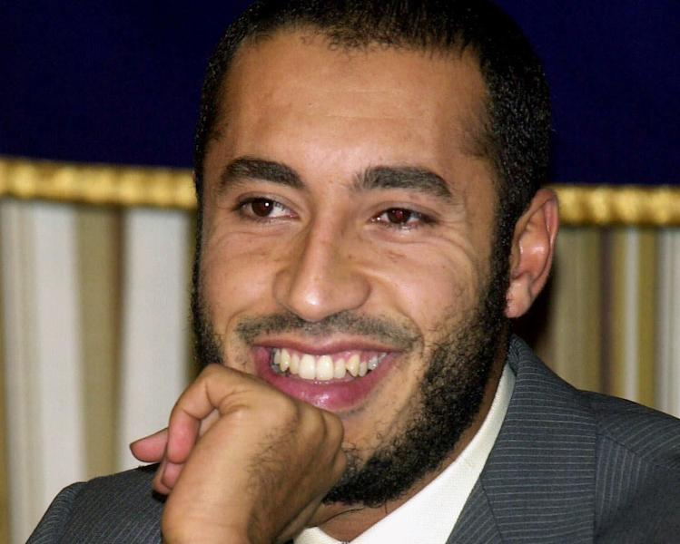 FILE - In this Tuesday, July 3, 2001 file photo, Al-Saadi Gadhafi, son of Libyan leader Moammar Gadhafi, smiles during a press conference at the Foreign Correspondents' Club of Japan in Tokyo. Libya says Niger has extradited Moammar Gadhafi's son al-Saadi, who fled as his father's regime crumbled in 2011 and who was under house arrest in the desert West African nation ever since. A Libyan official, who spoke on condition of anonymity in line with regulations, says al-Saadi arrived early on Thursday March 6, 2014 at the Tripoli airport and was transferred to a prison in the capital. (AP Photo/Tsugufumi Matsumoto, File)