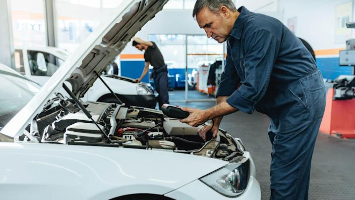 Car mechanic with diagnostic device for reading the error codes.