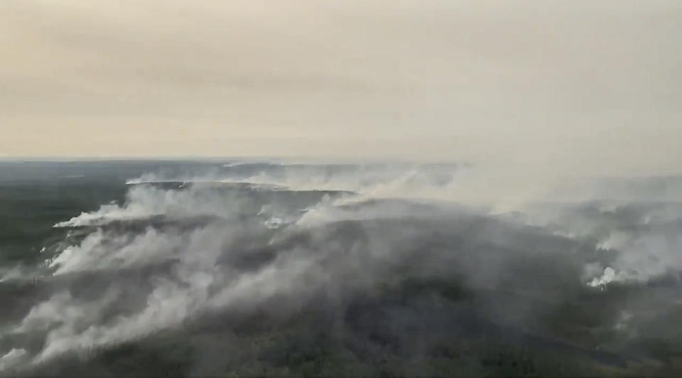 In this grab taken from video released by the Russian Defense Ministry Press Service, an air view of smoke from a forest fire in the republic of Sakha also knows as Yakutia, Russia Far East, Saturday, July 17, 2021. The Russian military has used its heavy-lift transport planes to help douse wildfires in Siberia. The Defense Ministry said Saturday that over the last 24 hours the crew of Il-76 military transport planes dropped water on forest fires in Yakutia in northeastern Siberia. The ministry said that military helicopters also dropped water to extinguish fires and also carried firefighters. (Russian Defense Ministry Press Service via AP)