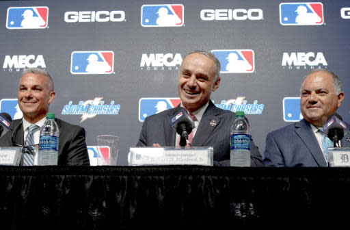 Baseball commissioner Rob Manfred, center, Al Avila, general manager of the Detroit Tigers, right, and Dayton Moore, general manager of the Kansas City Royals, participate in a news conference in Omaha, Neb., Thursday, June 21, 2018, to announce the Detroit Tigers will play the Kansas City Royals in Omaha the week the 2019 College World Series opens. (AP Photo/Nati Harnik)