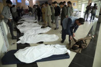 Afghan men try to identify the dead bodies at a hospital after a bomb explosion near a school west of Kabul, Afghanistan, Saturday, May 8, 2021. A bomb exploded near a school in west Kabul on Saturday, killing several people, many them young students, an Afghan government spokesmen said. (AP Photo/Rahmat Gul)