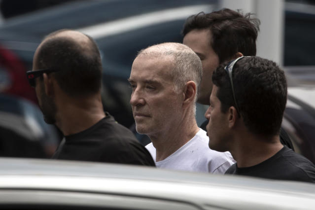 FILE - In this Jan. 31, 2017 file photo, businessman Eike Batista, flanked by police, arrives at the Federal Police headquarters in Rio de Janeiro, Brazil. Batista was found guilty of market manipulation by a Brazilian court on Monday, Sept. 30, 2019. He has been sentenced to eight years and seven months in prison. (AP Photo/Felipe Dana, File)